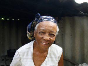 Seniorin, schaut mit einem großen Lächeln in die Kamera, hat ein Tuch um den Kopf gebunden