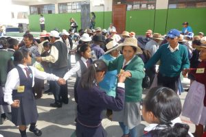 Ältere Menschen und Schulkinder tanzen bei einer gemeinsamen Aufführung in Peru