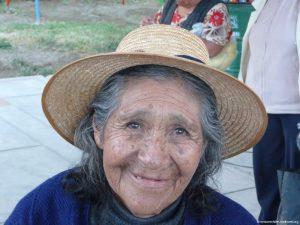 Seniorin, trägt einen Hut, lächelt in die Kamera
