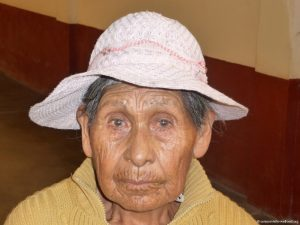 Seniorin, hat einen Hut aufgesetzt und schaut in die Kamera