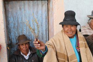 Seniorin aus Peru hält lächelnd Heilkräuter in die Kamera