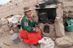 Alte Peruanerin sitzend vor Lehmofen im Freien