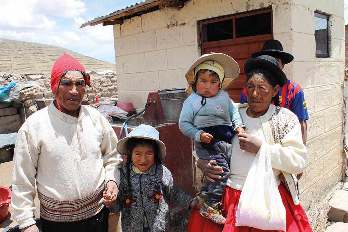 Peruanische Familie, Großeltern mit Kindern vor Steinhaus