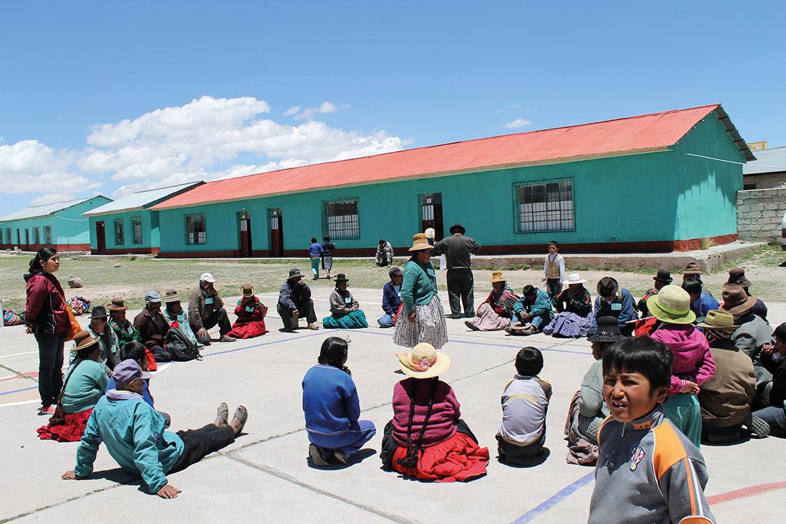 Peruaner im Kreis sitzend vor Gebäude