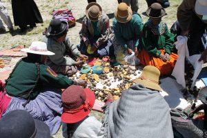 Peruaner im Kreis sitzend bereiten gemeinsam Essen vor