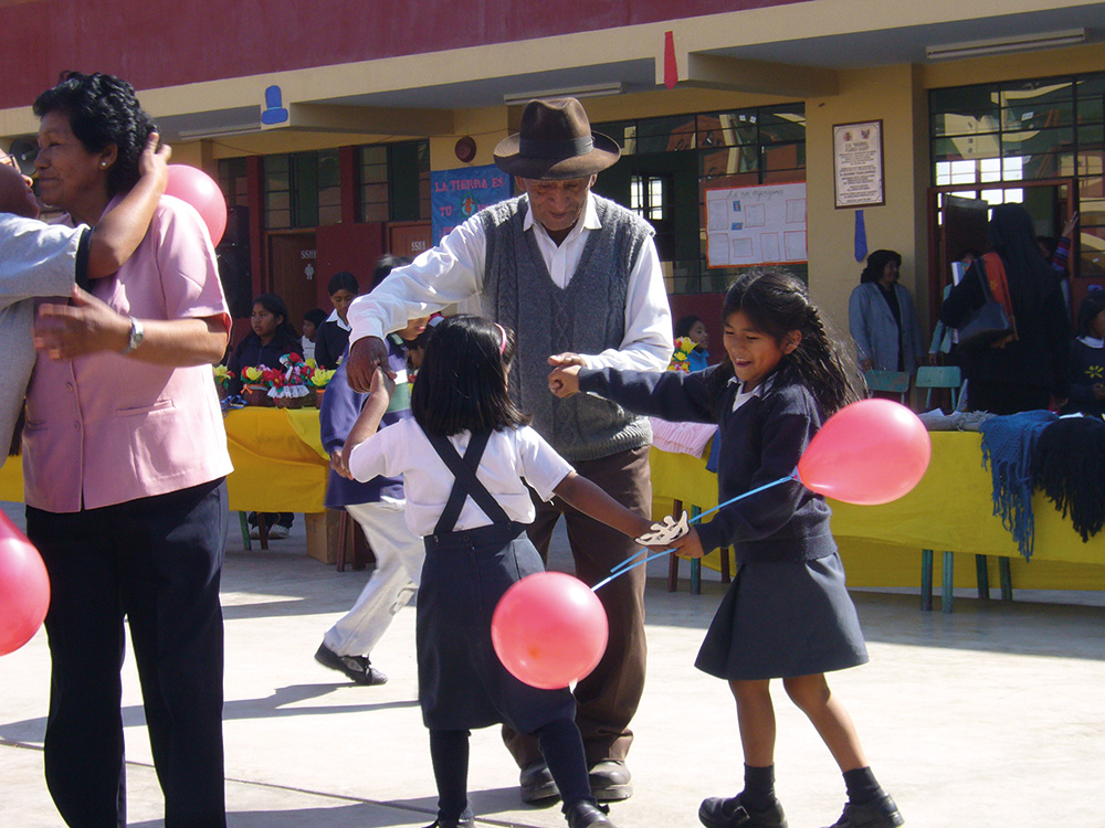 Älterer Peruaner tanzt mit Kindern, Luftballons in der Hand haben